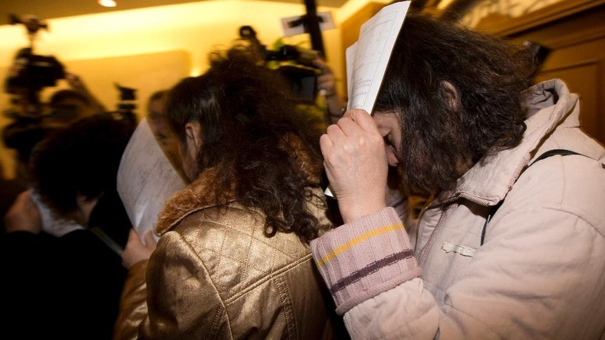 Chinese relatives of passengers aboard a missing Malaysia Airlines plane use application documents to block their faces as they walk out a hotel room in Beijing Monday, March 10, 2014. The anguished hours had turned into a day and a half. Fed up with awaiting word on the missing plane, relatives of passengers in Beijing lashed out at the carrier with a handwritten ultimatum and an impromptu news conference. (AP Photo/Andy Wong)