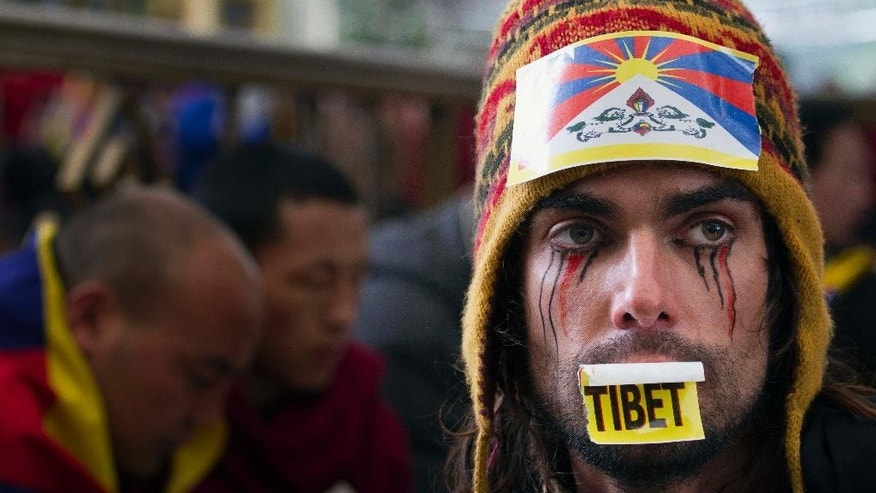 Austrian national Maximilian with a Tibetan flag attached to his hat joins exiled Tibetans at a gathering to mark the 55th anniversary of the failed uprising in the Tibetan capital Lhasa in 1959, in Dharmsala, India, Monday, March 10, 2014. The uprising of the Tibetan people against the Chinese rule was brutally quelled by Chinese army forcing the spiritual leader the Dalai Lama and hundreds of Tibetans to come into exile. (AP Photo/Ashwini Bhatia)