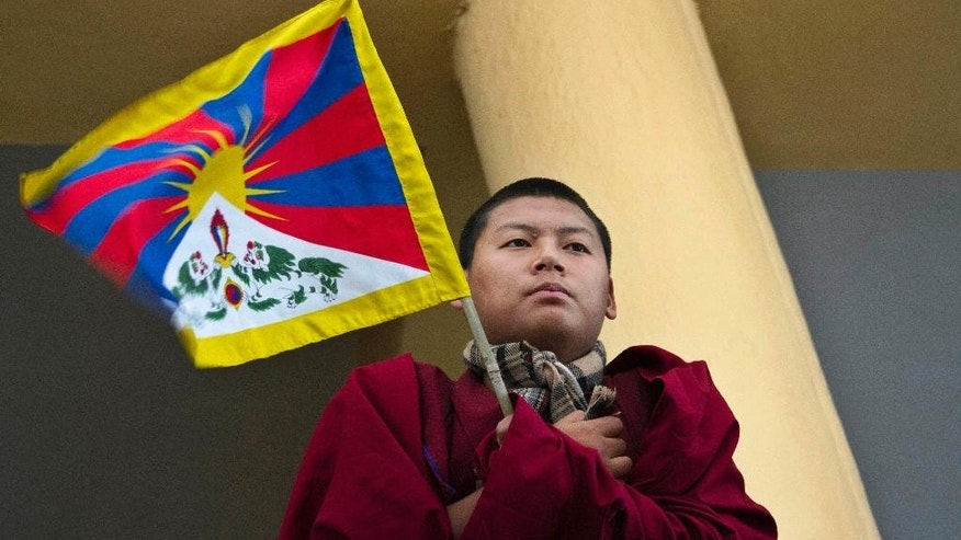 A young exile Tibetan monk holds a Tibetan flag during a gathering to mark the 55th anniversary of the failed uprising in the Tibetan capital Lhasa in 1959, in Dharmsala, India, Monday, March 10, 2014. The uprising of the Tibetan people against the Chinese rule was brutally quelled by Chinese army forcing the spiritual leader the Dalai Lama and hundreds of Tibetans to come into exile. (AP Photo/Ashwini Bhatia)