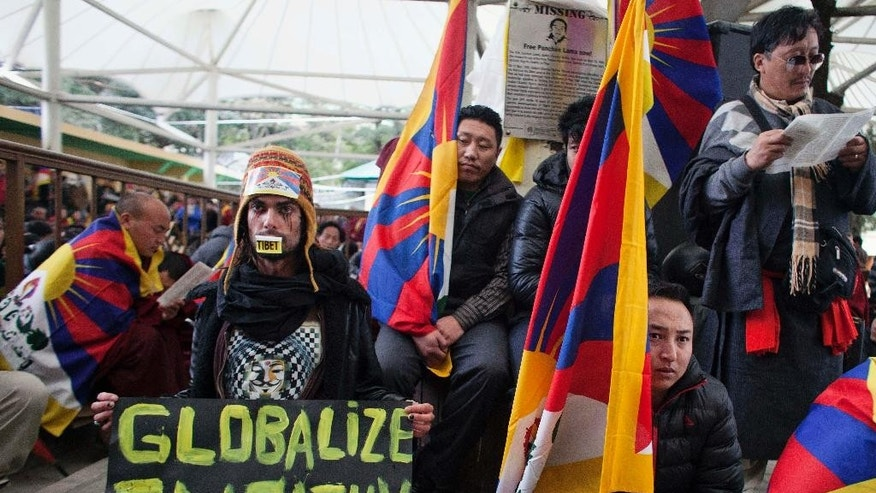 Austrian national Maximilian, foreground left, joins exile Tibetans during a gathering to mark the 55th anniversary of the failed uprising in the Tibetan capital Lhasa in 1959, in Dharmsala, India, Monday, March 10, 2014. The uprising of the Tibetan people against the Chinese rule was brutally quelled by Chinese army forcing the spiritual leader the Dalai Lama and hundreds of Tibetans to come into exile. (AP Photo/Ashwini Bhatia)