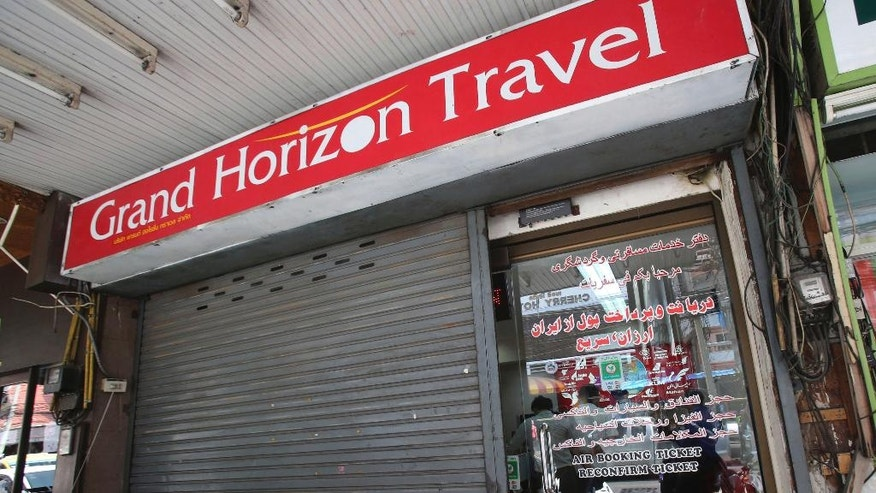 A man sits in front of closed door of the Grand Horizon Travel office in Pattaya, Chonburi province, Thailand, Monday, March 10, 2014. Thai police said owners of the travel agency told them they had received orders from a China Southern Airlines office in Bangkok for Malaysia Airlines flight MH370 for two individuals who boarded the flight with fake passports. (AP Photo/Sakchai Lalit)