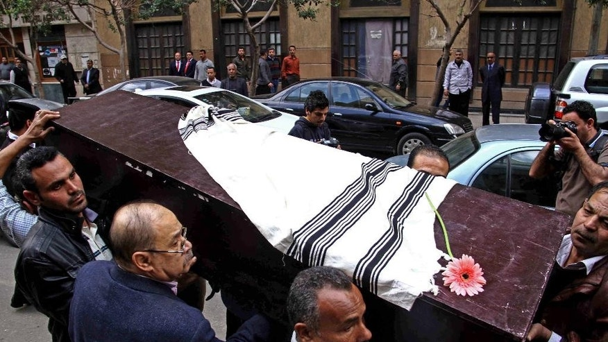 Egyptians carry the coffin of Nadia Haroun, the deputy head of the dwindling Jewish community, outside the Jewish synagogue, Shaar Hashamayim in Cairo, Egypt, Tuesday, March 11, 2014. Haroun, died of a heart attack last week. She was 59. Haroun, among the youngest in the aging and shrinking community, was a lawyer and an architect. (AP Photo/Ahmed Gomaa)