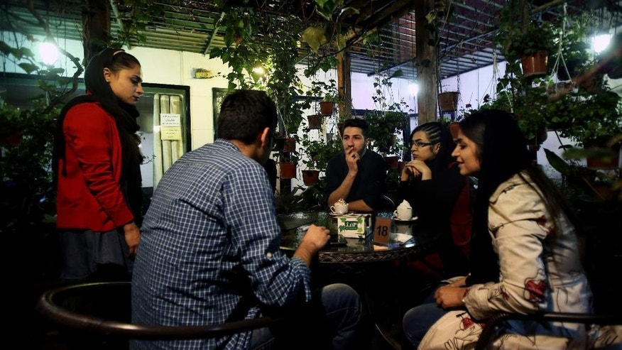 "In this Tuesday, March 4, 2014 photo, young Iranian adults sit at a cafe in Tehran, Iran. For years Iranian authorities kept the number of cafes limited since they were seen as a symbol of Western influence and places to spread non-Islamic beliefs. But reports of cafes being shut because they violate ""Islamic dignities"" have dropped markedly in recent months, suggesting a growing tolerance by the authorities. (AP Photo/Vahid Salemi)"