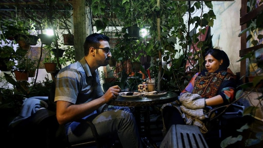 "In this Tuesday, March 4, 2014 photo, an Iranian woman meets with her friend at a cafe in Tehran, Iran. For years Iranian authorities kept the number of cafes limited since they were seen as a symbol of Western influence and places to spread non-Islamic beliefs. But reports of cafes being shut because they violate ""Islamic dignities"" have dropped markedly in recent months, suggesting a growing tolerance by the authorities. (AP Photo/Vahid Salemi)"