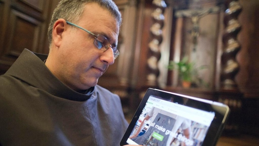 The head of the Franciscan convent of St. Francesco a Ripa, Friar Stefano Tamburo, uses a tablet device to check the Kickstart page promoting the conservation works required in the cell that St. Francis of Assisi is believed to have used when visiting the convent in Rome, Friday, Feb. 28, 2014. The friars who run the St. Francis a Ripa church in Rome's Trastevere neighborhood are launching a Kickstarter online fundraising campaign Tuesday, March 11, 2014, to try to raise the $125,000 to restore the tiny cell where St. Francis stayed when he came to Rome to see the pope, The Associated Press has learned. Rather than ask for funding from the Italian government, which owns the church and is responsible for its upkeep, the friars decided on this more democratic crowdfunding initiative thinking it more in keeping with the Franciscan tradition of seeking alms for just what they need, spreading the faith as they beg, and making sure the poor are the priority. (AP Photo/Domenico Stinellis)