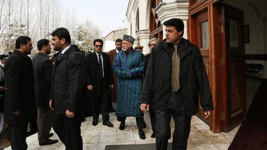 Afghan President Hamid Karzai, center, leaves after attending the funeral procession of Afghanistan's influential Vice President Mohammad Qasim Fahim in Kabul, Afghanistan, Tuesday, March 11, 2014. Fahim, a leading commander in the alliance that fought the Taliban who was later accused with other warlords of targeting civilian areas during the country's civil war, died on Sunday, March 9, 2014. He was 57. (AP Photo/Rahmat Gul)