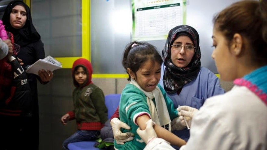 Dec. 18, 2013: This file photo shows a Syrian girl weeping after receiving the measles vaccine from UNICEF nurses Nadine Houjairi, second right, and Genivieve Bashalani, right, at the U.N. refugee agency's registration center in Zahleh, in Lebanon's Bekaa Valley.