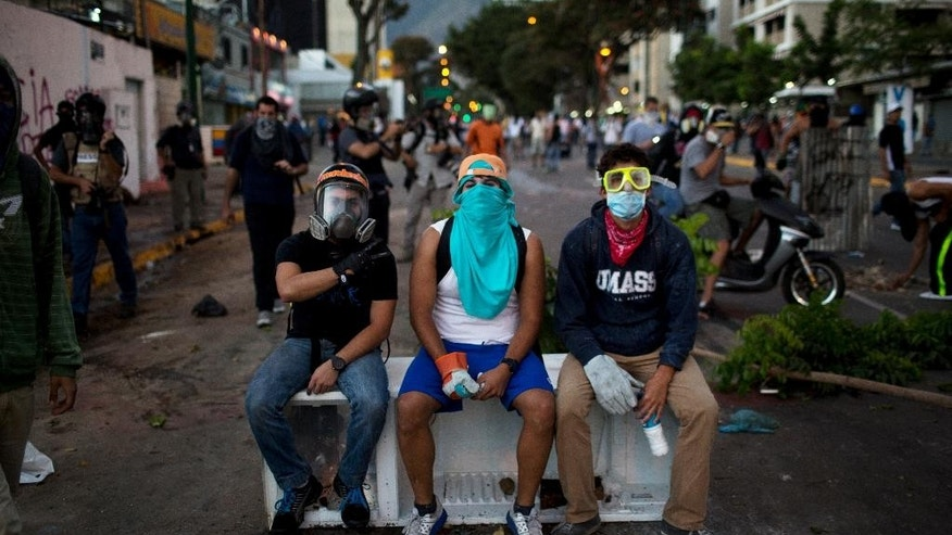 In this March 2, 2014 photo, anti-government demonstrators take a break on an old refrigerator used to build a barricade during clashes with security forces in Caracas, Venezuela. Fashion is not foreign to the young demonstrators who skirmish nearly nightly with security forces at the barricades in the Venezuelan capital. Painter and dust masks are common protection against tear gas, as are ski, scuba and swim goggles. (AP Photo/Rodrigo Abd)