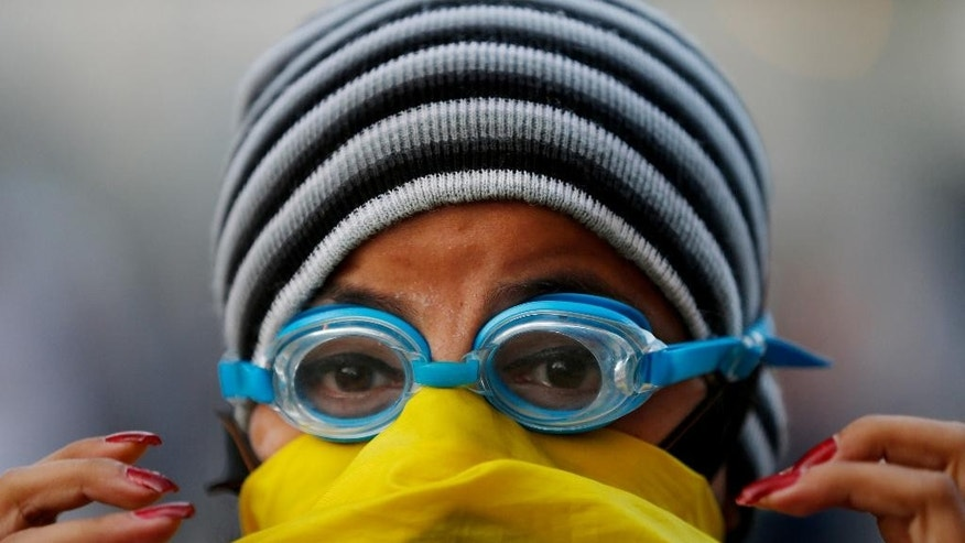 In this March 4, 2014 photo, an anti-government demonstrator wears swimming goggles to protect against the effects of tear gas during clashes with security forces in Plaza Altamira, Caracas, Venezuela. Identities are hidden by sparkly Carnival masks or simply a cloth wrapped around the face. (AP Photo/Fernando Llano)