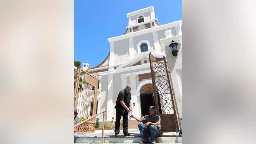 In this March 2, 2014 photo, a man gives money to a beggar after Mass outside the San Felipe Cathedral in the Arecibo Diocese in Arecibo, Puerto Rico. Prosecutors are pursuing more than a dozen sex abuse cases in Puerto Rico, including those of six priests defrocked by the Diocese of Arecibo. (AP Photo/Danica Coto)