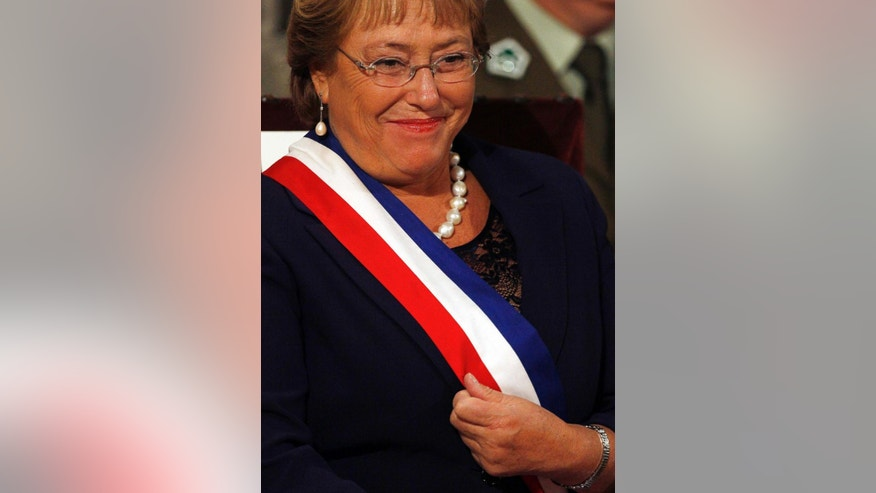 Chile's new President Michelle Bachelet adjusts her presidential sash during a religious ceremony in Santiago, Chile, Wednesday, March 12, 2014. Bachelet, who led Chile from 2006-2010, was sworn-in as president on Tuesday. (AP Photo/Luis Hidalgo)
