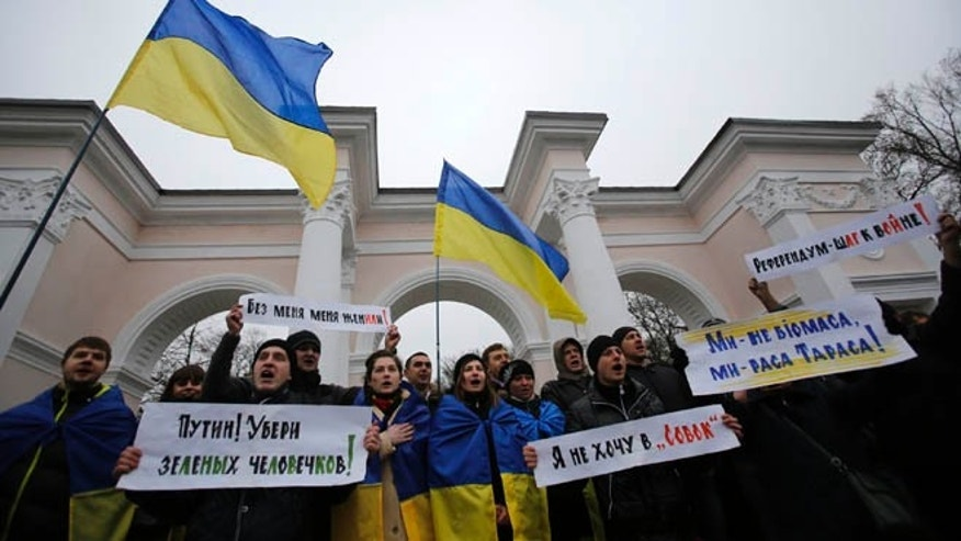 "March 11, 2014: People hold Ukrainian flags and banners that read: ""Putin! Take away the green men"", ""They got me married without me being there"", ""Referendum is a step to war"", during a rally against the breakup of the country in Simferopol, Crimea, Ukraine."