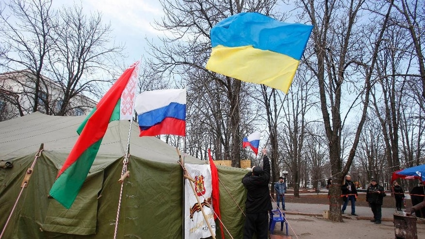 In this photo taken Tuesday, March 11, 2014, a man places a Ukrainian flag atop a tent alongside flags from Russia, center, and Belarus, left, at a tent camp set up by pro Russia activists in Luhansk, eastern Ukraine. Luhansk was home to one of the Soviet Union's blue-ribbon factories that turned out locomotives deemed good enough to be designated IS--the Russian-language initials of Josef Stalin. Since Russian troops rolled into Crimea, and lawmakers there scheduled a referendum for Sunday on whether to join Russia, the world's attention has focused on the fate of the lush peninsula that juts into the Black Sea. But here in Ukraine's coal-fired industrial east, where Russians have lived for more than two centuries, a potent mix of economic depression, ethnic solidarity and nostalgia for the certainties of the Soviet past have many demanding the right to become part of Russia as well.(AP Photo/Sergei Grits)