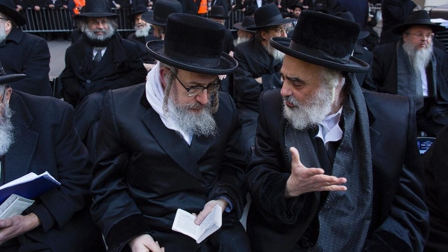 Rabbis speaks to one another as they joined other Orthodox Jews  in New York, Sunday, March 9, 2014, on Water Street in lower Manhattan, to pray and protest against the Israeli government's proposal to pass a law that would draft strictly religious citizens into its army. (AP Photo/Craig Ruttle)
