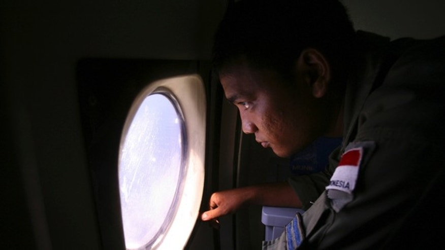 "An Indonesian Navy crew member scans the water bordering Indonesia, Malaysia and Thailand during a search operation for the missing Malaysian Airlines Boeing 777 near the Malacca straits on Monday, March 10, 2014. Dozens of ships and aircraft have failed to find any piece of the missing Boeing 777 jet that vanished more than two days ago above waters south of Vietnam as investigators pursued ""every angle"" to explain its disappearance, including hijacking, Malaysia's civil aviation chief said Monday. (AP Photo/Binsar Bakkara)"