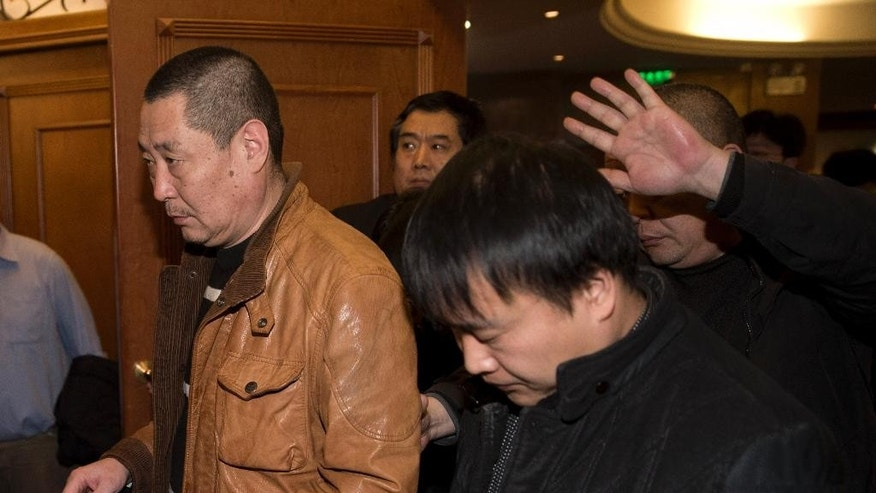 Chinese relatives of passengers aboard a missing Malaysia Airlines plane walk out from a hotel room after meeting with Malaysian officials, in Beijing, China Wednesday, March 12, 2014. The missing Malaysian jetliner may have attempted to turn back before it vanished from radar, but there is no evidence it reached the Strait of Malacca, Malaysia's air force chief said Wednesday, denying reported remarks he said otherwise. The statement suggested continued confusion over where the Boeing 777 might have ended up, more than four days after it disappeared en route to Beijing from Kuala Lumpur with 239 people on board. (AP Photo/Andy Wong)