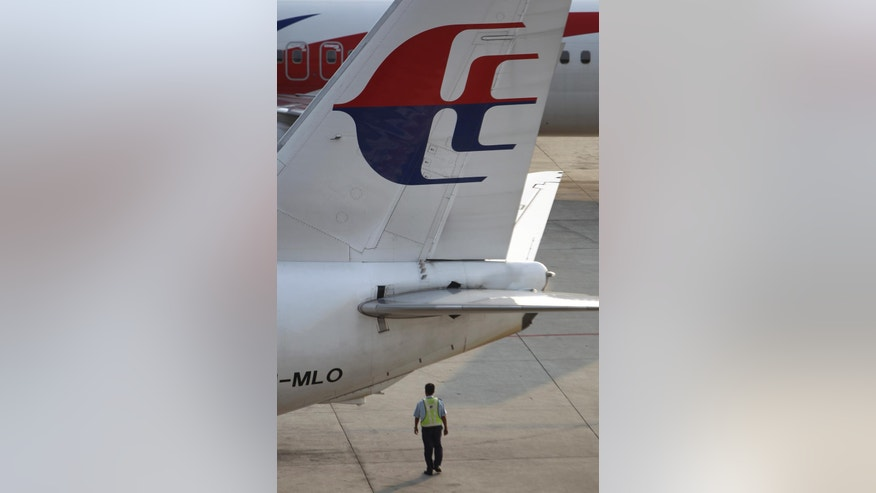 A ground staff member walks under a Malaysia Airlines plane at Kuala Lumpur International Airport in Sepang, Malaysia, Wednesday, March 12, 2014. The missing Malaysian jetliner may have attempted to turn back before it vanished from radar, but there is no evidence it reached the Strait of Malacca, Malaysia's air force chief said Wednesday, denying reported remarks he said otherwise. The statement suggested continued confusion over where the Boeing 777 might have ended up, more than four days after it disappeared en route to Beijing from Kuala Lumpur with 239 people on board. (AP Photo/Lai Seng Sin)