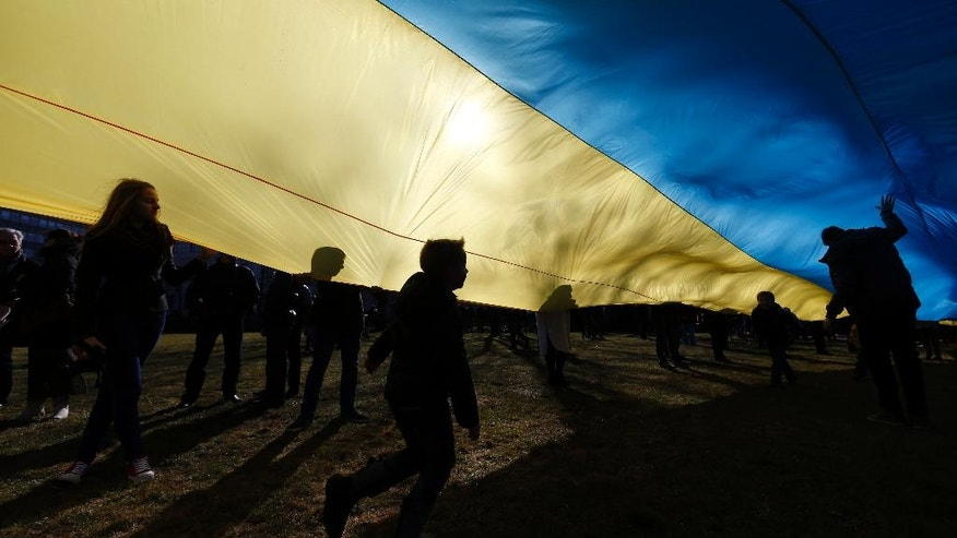 Children play as people hold up a giant Ukrainian flag to protest against the Russian intervention in Ukraine during the celebration of Lithuania's independence in Vilnius, Lithuania, Tuesday March 11, 2014. Lithuania celebrated the anniversary of its declaration of independence from the Soviet Union on Thursday, recalling the seminal events that set the Baltic nation on a path to freedom and helped lead to the collapse of the U.S.S.R. (AP Photo/Mindaugas Kulbis)