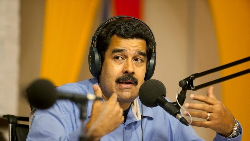 "Venezuela's President Nicolas Maduro speaks during a radio and television program called ""In contact with Maduro"", at the Miraflores presidential palace in Caracas, Venezuela, Tuesday, March 11, 2014. Venezuelan President Nicolas Maduro canceled plans to be at the innauguration of Chile's President Michelle Bachelet, after Biden called the street protests in Venezuela ""alarming"" and said democratically elected leaders who rule as authoritarians damage their people and countries. (AP Photo/Alejandro Cegarra)"