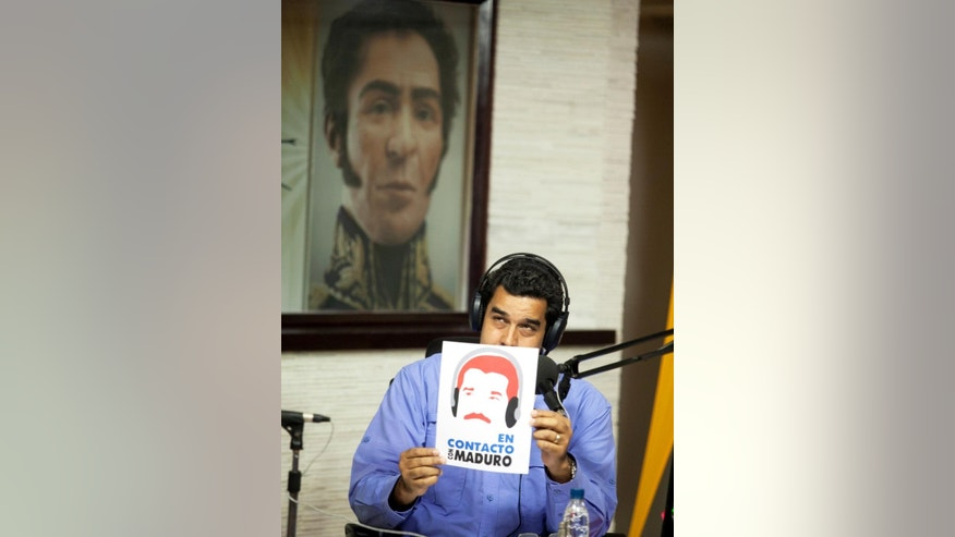 "Venezuela's President Nicolas Maduro holds up the logo of his radio and television program ""In contact with Maduro"", at Miraflores presidential palace in Caracas, Venezuela, Tuesday, March 11, 2014. President Maduro canceled plans to be at the inauguration of Chile's President Michelle Bachelet, after U.S. Vice President Joe Biden called the street protests in Venezuela ""alarming"" and said democratically elected leaders who rule as authoritarians damage their people and countries.  (AP Photo/Alejandro Cegarra)"
