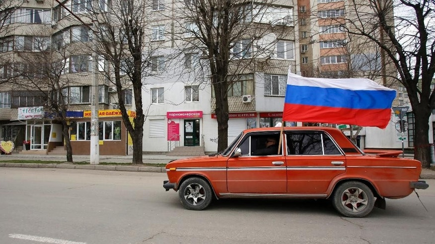 FILE - In this Saturday, March 8, 2014 file photo, a car with a Russian national flag drives through Simferopol, Ukraine. Russia fever is everywhere in the streets of Crimea - from the men who hawk Russian tricolor flags to drivers at traffic lights to the mini-vans that belt out patriotic songs to the World War II bunker that has become a drop-off point for people to donate blankets and canned food for armed militiamen who patrol the streets. (AP Photo/Darko Vojinovic, File)