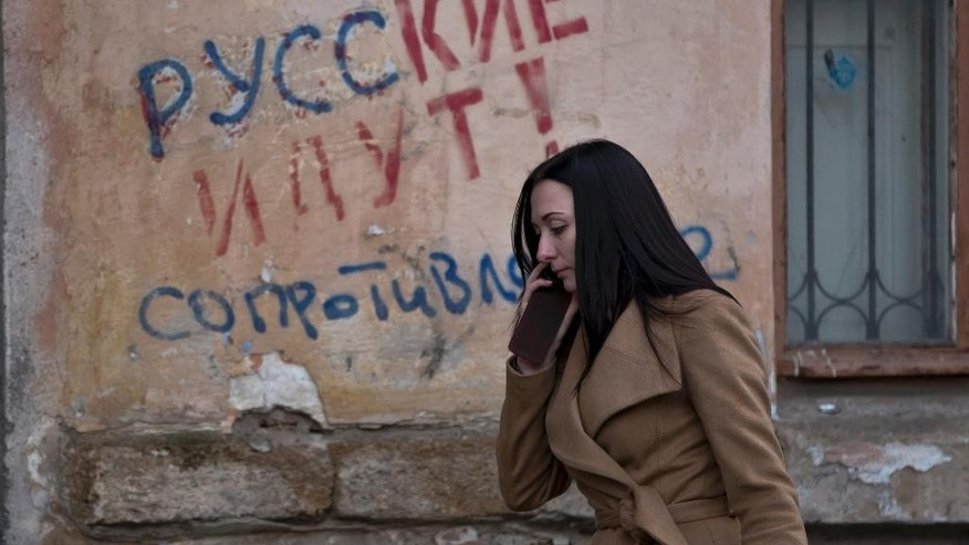"FILE - In this Friday, March 7, 2014 file photo, a woman passes by a graffiti that reads ""The Russians are coming - Resistance"" in Simferopol, Ukraine. For the ethnic Ukrainians and Tatars who are the minority in the strategic peninsula, it is fear that dominates days before Crimea votes in a referendum on joining Russia. (AP Photo/Vadim Ghirda, File)"