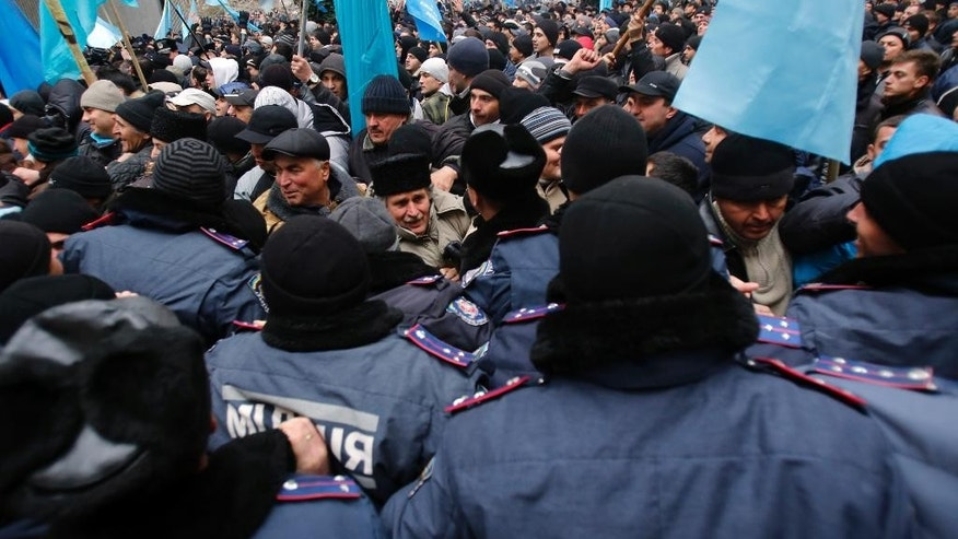 FILE - In this Wednesday, Feb. 26, 2014 file photo, Crimean Tatars, at back, clash with police in front of a local government building in Simferopol, Ukraine. For the ethnic Ukrainians and Tatars who are the minority in the strategic peninsula, it is fear that dominates days before Crimea votes in a referendum on joining Russia. (AP Photo/Darko Vojinovic, File)