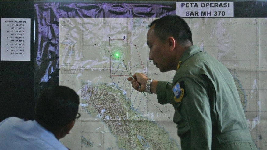 Indonesian Air Force officers examine a map of the Malacca Strait during a briefing following a search operation for the missing Malaysia Airlines Boeing 777, at Suwondo air base in Medan, North Sumatra, Indonesia, Wednesday, March 12, 2014. Malaysia asked India to join the expanding search for the missing jetliner near the Andaman Sea,  far to the northwest of its last reported position and a further sign Wednesday that authorities have no idea where the plane might be more than four days after it vanished. (AP Photo/Binsar Bakkara)