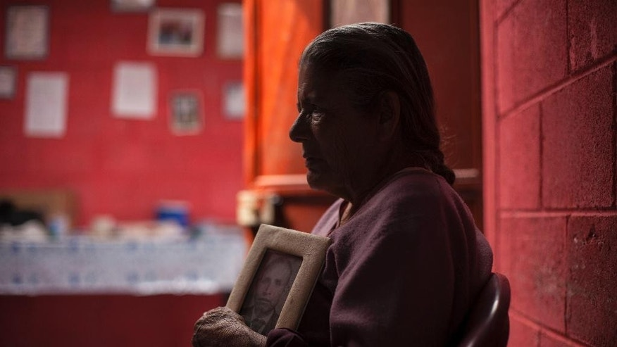 In this March 6, 2014 photo, Austina Machic, 76 years-old, holds a portrait of her late husband Horacio Tajtaj Callejas during an interview at her home in San Andres Itzapa, Guatemala. In November 1988 in the mountainous area of western Guatemala, 22 men who lived in the village of El Aguacate where massacred by leftists guerillas during the Guatemalan civil war. The case will be taken to court on Thursday March 13, 2014 in which more than 30 persons are expected to testify. Horacio Tajtaj Callejas was killed in the massacre. (AP Photo/Luis Soto)
