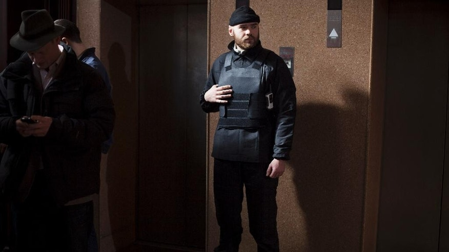In this photo taken Friday, March 7, 2014, a Right Sector member stands guard next to elevators on the ground floor of the Dnipro hotel near the Independence Square, Kiev, Ukraine. The vocal and well-armed organization presents a headache for the new Ukrainian leadership with its armed presence in the streets, its radical nationalist rhetoric and its antics. (AP Photo/David Azia)