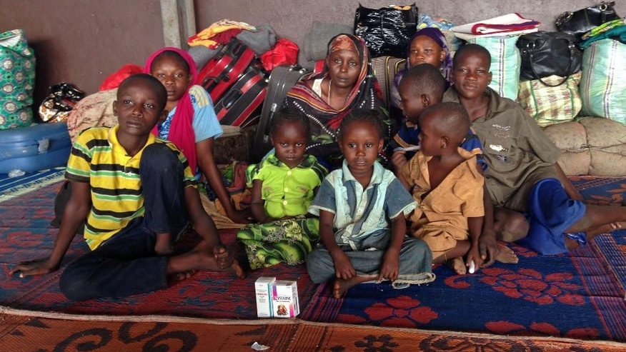 In this photo taken on Friday March 7, 2014, Yaman Ahmat, center, sits with her children at Bangui Airport after only hours earlier, her husband Marcus Madi, had put her and their eight children including newborn daughter Ashta onto a flight to the capital in a desperate bid to save their lives, but he was tragically killed on his return from the airport. The two married when they were 17-year old and now have a large family, but Marcus Madi had to return to sell what remained of his store merchandise before leaving to join his family in safety, but he died in a hail of gunfire, leaving his family with their belongings packed into the bags behind them at the airport.  (AP Photo/Krista Larson)