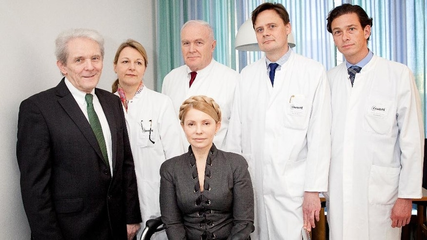 In this picture publicly provided by the Charite hospital in Berlin, former Ukrainian Prime Minister Yulia Tymoshenko , center,  poses  with her doctors  Professor  Karl Max Einhaeupl , left,  CEO of the Charite Hospital and doctors from left :  Dr. Anett Reisshauer , Professor  Nobert Haas, Professor Matthias Endres, and Professor Peter Vajkoczy in the Charite Hospital in Berlin, Germany,  on Saturday March 8,  2014.  Ukraine's former prime minister, Yulia Tymoshenko, has started medical treatment at Berlin's Charite hospital after arriving late Friday, but doctors treating her say it's too soon to say how long this will take. (AP Photo/ho/Charite Universitaetsmedizin Berlin) MANDATORY CREDIT