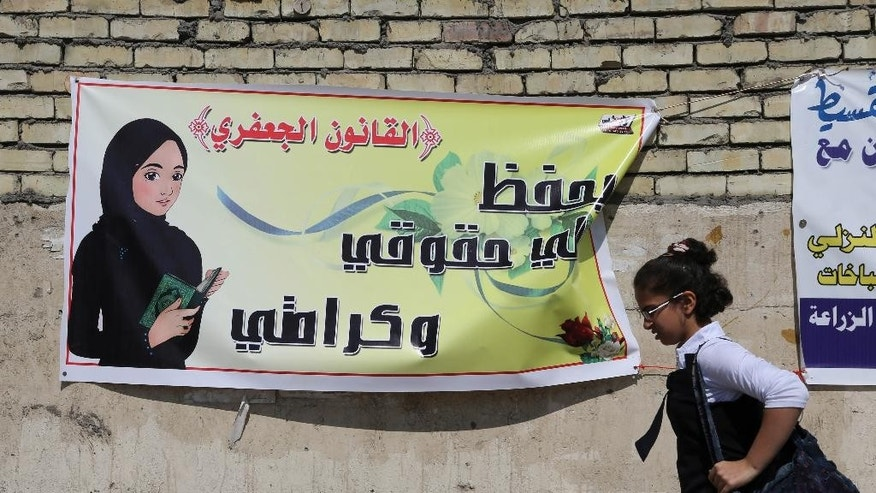 "In this Thursday, March 13, 2014 photo, a schoolgirl passes by a banner for the Jaafari Personal Status Law in Baghdad, Iraq. The Arabic on the banner reads, ""the Jaafari Personal Status Law saves my rights and my dignity."" A contentious civil status draft law for Iraqi Shiite community that allows child marriage and restricts women's rights has stirred up a row among many Iraqis who see it as a setback for child and women rights, threatening to add more divisions and woos to the society that is already in fragments. (AP Photo/Karim Kadim)"