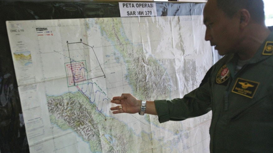 "Lt. Col Bambang Sudewo, commander of the 5th Air Squadron ""Black Mermaids"" examines a map following a search operation for the missing Malaysia Airlines Boeing 777 that was conducted over the Strait of Malacca, at Suwondo air base in Medan, North Sumatra, Indonesia, Friday, March 14, 2014. The jetliner vanished nearly a week ago with 239 people aboard. (AP Photo/Binsar Bakkara)"