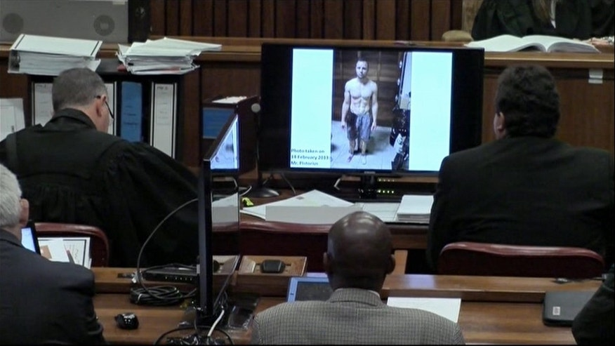A police photograph of Oscar Pistorius standing on his blood-stained prosthetic legs and wearing shorts covered in blood.