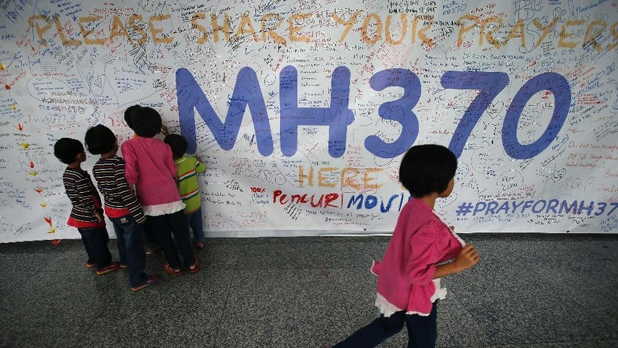 Children read messages and well wishes displayed for all involved with the missing Malaysia Airlines jetliner MH370 on the walls of the Kuala Lumpur International Airport, Thursday, March 13, 2014 in Sepang, Malaysia. Planes sent Thursday to check the spot where Chinese satellite images showed possible debris from the missing Malaysian jetliner found nothing, Malaysia's civil aviation chief said, deflating the latest lead in the six-day hunt. The hunt for the missing Malaysia Airlines flight 370 has been punctuated by false leads since it disappeared with 239 people aboard about an hour after leaving Kuala Lumpur for Beijing early Saturday. (AP Photo/Wong Maye-E)