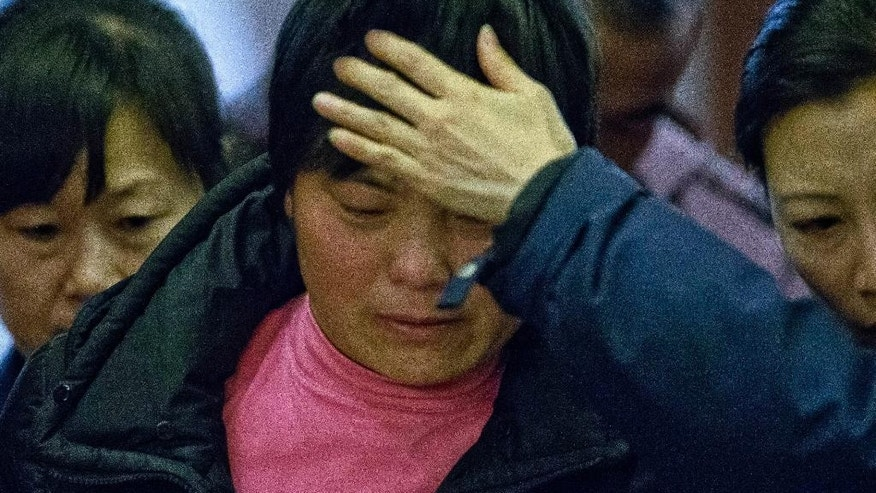 A crying woman, one of the relatives of Chinese passengers aboard missing Malaysia Airlines Flight MH370, is assisted by volunteers as she leaves a hotel ballroom where families were briefed on rescue and searching efforts in Beijing, China, Friday, March 14, 2014. (AP Photo/Alexander F. Yuan)