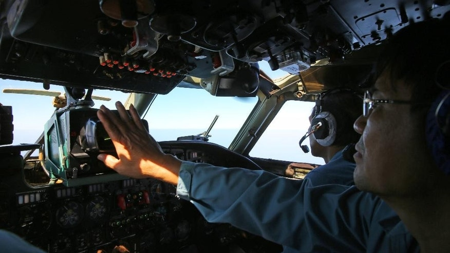 A cabin crew of the Vietnam Air Force is seen onboard a flying AN-26 Soviet made aircraft during a search operation for the missing Malaysia Airlines flight MH370 plane over the southern sea between Vietnam and Malaysia Friday, March 14, 2014. Vietnam says it has downgraded but not stopped its search for the missing jetliner in the South China Sea and has been asked by Malaysian authorities to consider sending planes and ships to the Strait of Malacca.  (AP Photo/Na Son Nguyen)