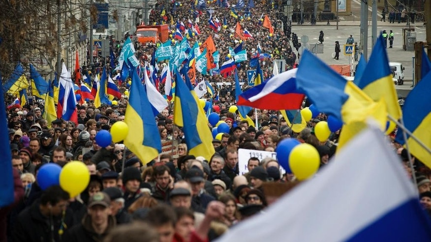 Demonstrators carrying Russian and Ukrainian flags march to oppose  president Vladimir Putin's policies in Ukraine, in Moscow, Saturday, March 15, 2014. Large rival marches have taken place in Moscow over Kremlin-backed plans for Ukraine's province of Crimea to break away and merge with Russia. More than 10,000 people turned out Saturday for a rally in the center of the city held to oppose what many demonstrators described as Russia's invasion of the Crimean Peninsula. In a nearby location, a similar sized crowd voiced its support for Crimea's ethnic Russian majority, who Moscow insists is at threat from an aggressively nationalist leadership now running Ukraine. (AP Photo/Alexander Zemlianichenko) (AP Photo/Alexander Zemlianichenko)