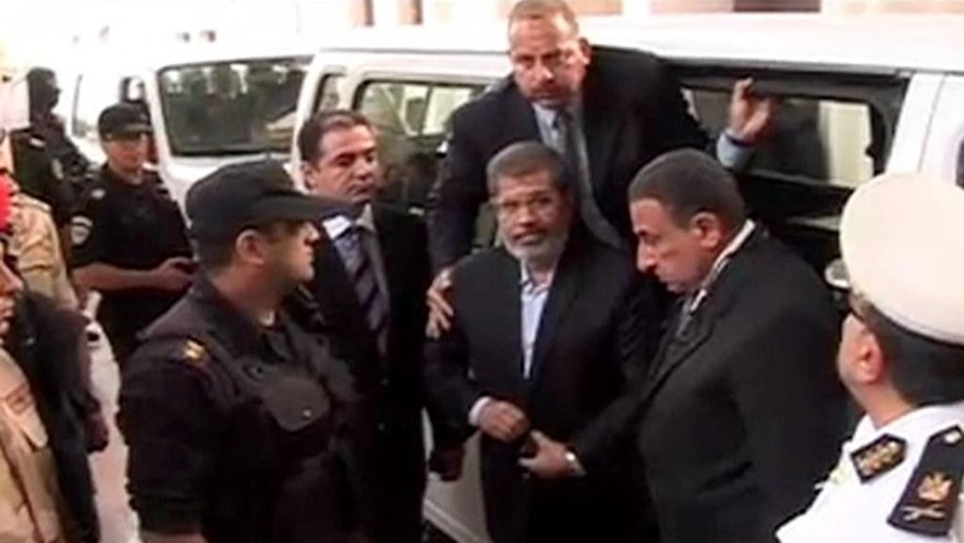 FILE - This Monday, Nov. 3, 2013 file image made from video provided by Egypt's Interior Ministry shows ousted President Mohammed Morsi, center, arriving for a trial hearing in Cairo, Egypt after four months in secret detention. Egypt's crackdown on Islamists has jailed 16,000 people over the past eight months in the country's biggest round-up in nearly two decades, according to previously unreleased figures from security officials. Rights activists say reports of abuses in prisons are mounting, with prisoners describing systematic beatings and miserable conditions for dozens packed into tiny cells. (AP Photo/Egyptian Interior Ministry, File)
