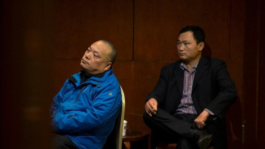 Chinese men watch TV after attending a briefing by Malaysia Airlines officials in a room reserved for relatives of passengers onboard the missing Malaysia Airlines flight MH370 at a hotel in Beijing, China Sunday, March 16, 2014. Attention focused Sunday on the pilots of the missing Malaysia Airlines flight after the country's leader announced findings so far that suggest someone with intimate knowledge of the Boeing 777's cockpit seized control of the plane and sent it off-course. (AP Photo/Andy Wong)