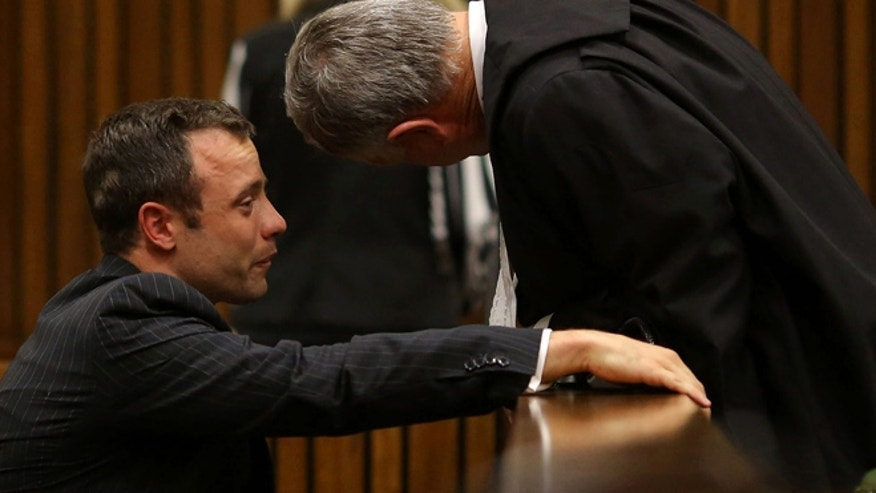 March 10, 2014: Oscar Pistorius, cries as he talks to his attorney, Barry Roux, right, after listening to evidence in cross questioning about the events surrounding the shooting death of his girlfriend Reeva Steenkamp, in court during his trial in Pretoria, South Africa.