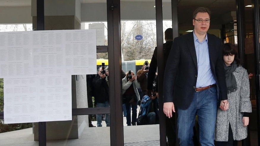 Serbian Progressive Party leader Aleksandar Vucic leaves a polling station with his daughter Milica after voting for the parliamentary elections in Belgrade, Serbia, Sunday, March 16, 2014. Serbs are voting in an early parliamentary election that is expected to tighten the grip on power of the ruling populists, who have become popular by promising to fight crime and corruption in the troubled Balkan nation seeking EU entry. (AP Photo/Darko Vojinovic)