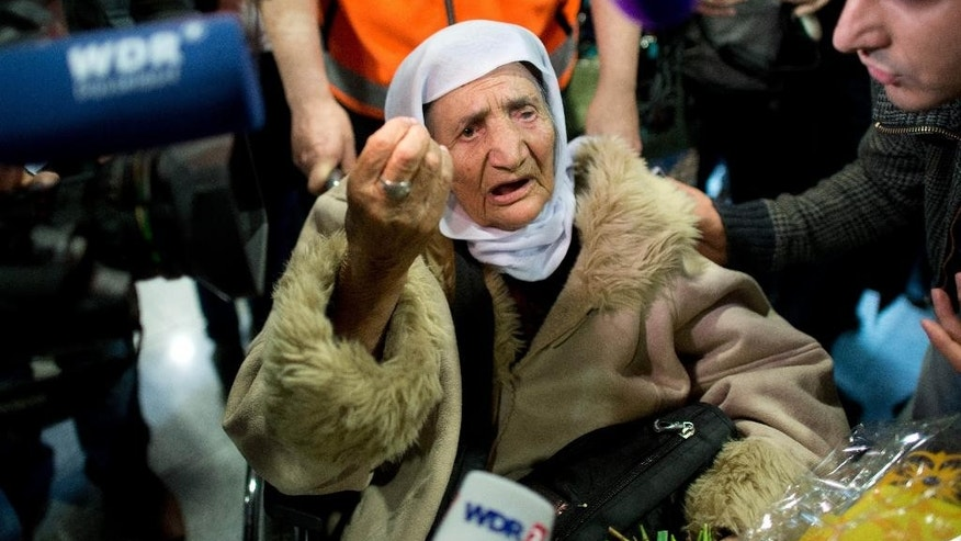 107-year-old Syrian Sabria Khalaf talks to reporters as she arrives at the airport in Duesseldorf, Germany, Monday, March 17, 2014. The woman who fled the conflict in Syria has been reunited with her family in Germany. German officials say Khalaf arrived from Greece where she had originally applied for asylum. (AP Photo/dpa, Federico Gambarini)