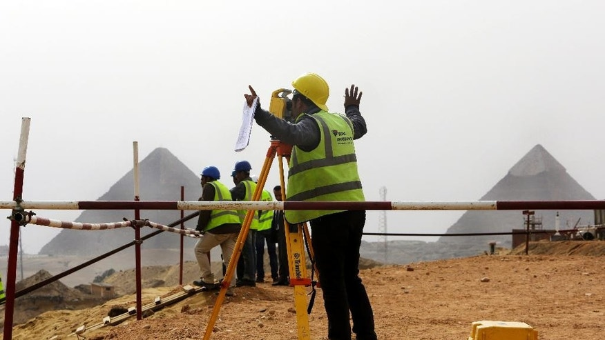 An Egyptian engineer gestures to his colleagues at the construction site of Egypt's Grand museum, just outside of Cairo, Monday, March 17, 2014. Egypt's antiquities minister says construction has begun on the main hall of a massive new museum by the Pyramids, the final phase of a complex that's intended to house 100,000 ancient artifacts including King Tutankhamun's mummy. (AP Photo/Amr Nabil)