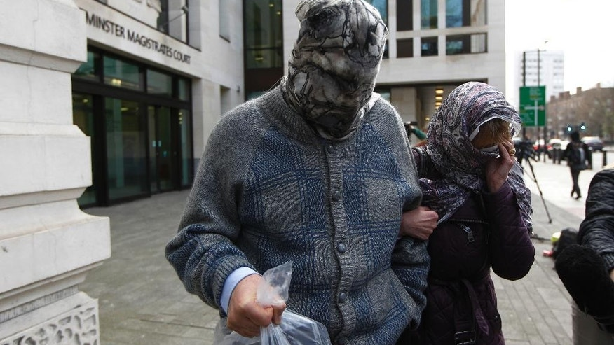 Convicted mafia boss Domenico Rancadore, left, and his wife Anne Skinner, with their faces covered leave Westminster Magistrates Court after he is granted bail while an appeal takes place for his extradition to Italy, Monday, March 17, 2014. (AP Photo/Sang Tan)