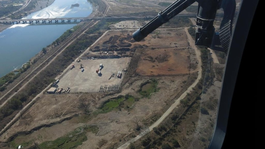 In this March 12, 2014, Mexican federal police fly over the Balsas River near the Pacific port of Lazaro Cardenas, Mexico. Alonso Ancira, president of the National Chamber of the Iron and Steel, told local media that drug cartels earned $1 billion in profits in 2013 from the sale of iron ore, according to his estimates. By 2012 nearly half of the iron ore exports to China went through the port of Lazaro Cardenas. The federal government took over the port of Lazaro Cardenas in November 2013. (AP Photo/Eduardo Castillo)