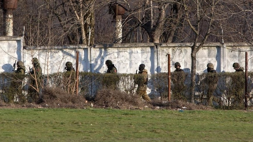 Unidentified armed men search an area close to an Ukrainian military unit in Simferopol, Crimea, on Tuesday, March 18, 2014. Gunfire at the military facility in the capital of separatist Crimea killed one serviceman and a member of a local self-defense brigade, a police spokeswoman was quoted as saying by the Interfax news agency. (AP Photo/Andrei Udovichenko)