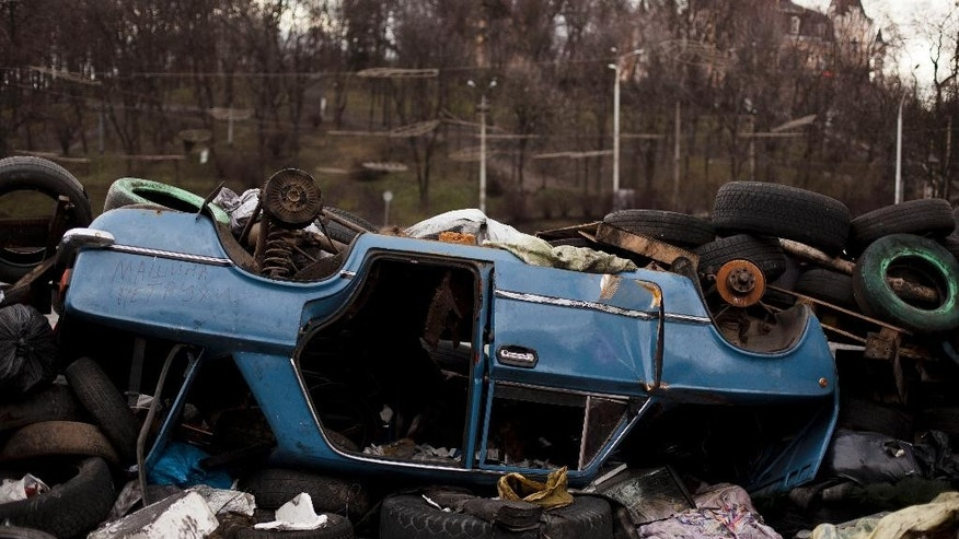 "The wreckage of a car is used to form part of a barricade on a road leading to Kiev's Independence Square, Ukraine, Tuesday, March 18, 2014. The words on the side of the car read in Russian, ""Peter's car"". (AP Photo/David Azia)"