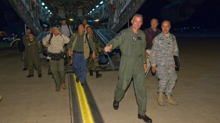 In a photo released by the the U.S. Air Force, Keith Stansell (3rd R) steps off the ramp of a C-17 Globemaster III July 2, 2008 at Lackland Air Force Base, Texas. Stansell, along with fellow military contractors Thomas Howes and Mark Gonsalves, was held captive for  five years by the Revolutionary Armed Forces of Colombia (FARC).